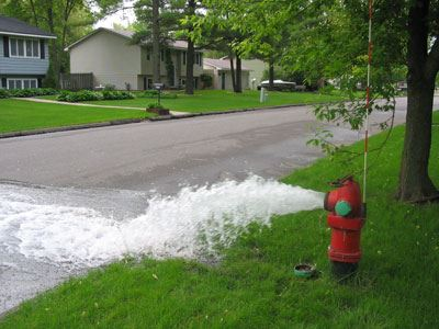 A water hydrant shooting a stream of water onto the street.